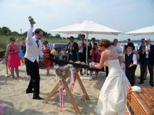 Hochzeitsbrauch - Holzstamm saegen am Strand